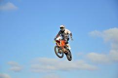 Motocroßmitfahrer in der Luft, Einhandoperation Stockfotografie