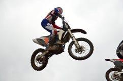 Motocroßmitfahrer fliegt durch Luft Lizenzfreies Stockfoto