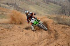 Motocroßmitfahrer mit einer starken Steigung dreht sich scharf Lizenzfreies Stockfoto