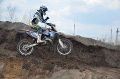 Motocroßmitfahrer springt über eine tönerne Grube Lizenzfreie Stockfotos