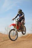 Motocroßmotorrad-Rennläufer führt einen Sprung durch Lizenzfreies Stockfoto