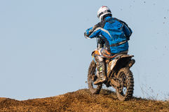 Motocross racer. With mud on motorbike climbing hill stock image