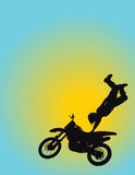 Motocross. Silhouette of a young man flying through the air on his motorcycle with one hand on the seat Stock Images