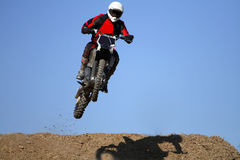 Motocross. Man jumping high in a motocross bike across a slope on a desert stock image