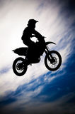Motocross. Rider making a jump in a dirt track race Royalty Free Stock Images