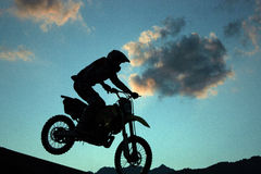 Motocross. Silhouette of an extreme driver of a motocross royalty free stock photo
