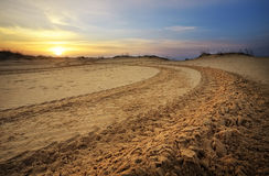 Motocross and auto sport track with sunset sky background. Wheel tracks on sand Stock Photo