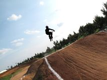 Motocross bicycle racer flying over obstacles Stock Image