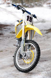Motocross bike. New yellow motocross bike on ice and snow on background stock photography