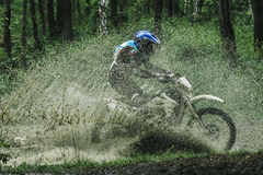 Motocross bike crossing creek, water splashing Royalty Free Stock Images