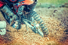 Motocross bike rear mud. Rear view of drifting motocross bike. The rear wheel is digging deep in the mud and throws dirt in the air. Focus is on the throwing Royalty Free Stock Images