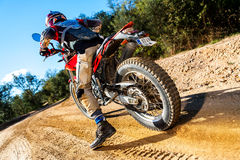 Motocross bike taking off on dirt road. Royalty Free Stock Images
