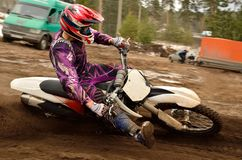 Motocross biker raised leg forward executes turnin Stock Image