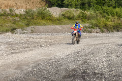 Motocross biker. A biker riding a motocross bike along a rural and stoned road stock images