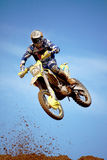 Motocross dirtbike in the air. View of a motorcross dirtbike on the dirt performing a jump Royalty Free Stock Image