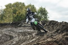 Motocross driver on race track. Motocross driver in action accelerating the motorbike after the corner on the race track Royalty Free Stock Images