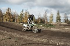 Motocross driver on race track. Motocross driver in action landing the motorbike after the jump on the race track Royalty Free Stock Images
