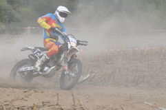 Motocross driver in dust Royalty Free Stock Photos