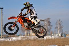 Motocross driver flies over hill out of snow Royalty Free Stock Images