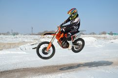 Motocross driver flies over hill out of snow Stock Images