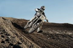 Motocross driver on race track. Motocross driver in action accelerating the motorbike after the corner on the race track Royalty Free Stock Photo