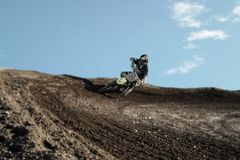 Motocross driver on race track. Motocross driver in action accelerating the motorbike after the corner on the race track Royalty Free Stock Photography