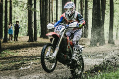 Motocross driver under the spray of mud Royalty Free Stock Photography