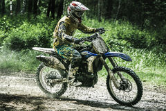 Motocross driver on wet and muddy terrain Stock Photos