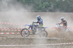 Motocross drivers in dust. Motocross Drivers  at stubble field motocross race Stock Images
