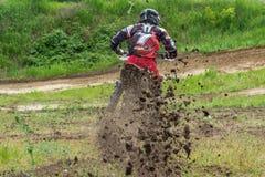 motocross El motorista acomete a lo largo de un camino de tierra, suciedad vuela de debajo las ruedas imagen de archivo libre de regalías