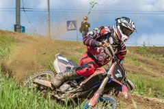 motocross El motorista acomete a lo largo de un camino de tierra, suciedad vuela de debajo las ruedas Vegetaci?n verde y cielo az imagen de archivo libre de regalías