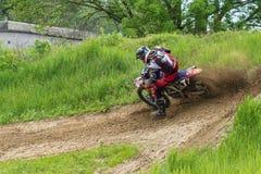 motocross El motorista en una curva acomete a lo largo de un camino de tierra, suciedad vuela de debajo las ruedas foto de archivo