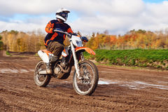 Motocross, enduro rider on dirt track. The forest behind him Stock Photo
