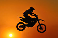 Motocross extreme sport. A motor cross rider in the air with a sunset background Stock Photography