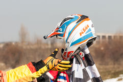 Motocross helmet. Hand take motocross helmet from finish flag Stock Photos