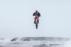 Motocross jeździec skacze nad górą Zdjęcia Royalty Free