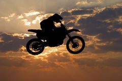 Motocross jump. Silhouette motocross bike jump in cloudy sky Royalty Free Stock Photo