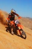 Motocross-Mitfahrer, der aus einer Ecke heraus anschält Lizenzfreie Stockfotografie