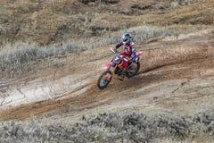 motocross Motocyklista w chyle śpieszy się wzdłuż drogi gruntowej, brud lata spod kół Zako?czenie obraz stock