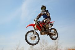 Motocross motorbike racer performs a jump. Efficient, hangs in the open air Royalty Free Stock Image