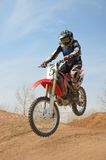 Motocross motorbike racer performs a jump Royalty Free Stock Photo
