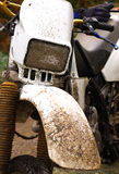 Motocross motorcycle covered in mud. Dirty white mx bike with gloves Royalty Free Stock Image