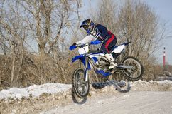 Motocross, motorcycle driver flies over hill out of snow Stock Photo