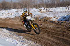 Motocross, motorcycle driver flies over hill out of snow Stock Photos