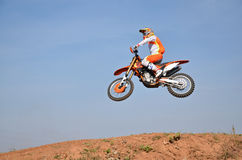Motocross, motorcycle driver flies over hill out of snow Royalty Free Stock Photography