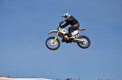 Motocross, motorcycle driver flies over hill out of snow Royalty Free Stock Photo