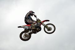 Motocross motorcycle racer flying high Stock Photo