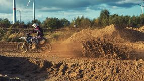 Motocross MX Rider riding on dirt track. Arnoldsweiler, Germany, October 05,2017:Extreme Motocross MX Rider riding on dirt track on a sunny late summer day on Stock Photos