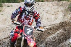 motocross O motociclista apressa-se ao longo de uma estrada de terra, sujeira voa de debaixo das rodas Contra o contexto de verde foto de stock