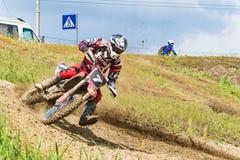 motocross O motociclista em uma curvatura apressa-se ao longo de uma estrada de terra, sujeira voa de debaixo das rodas fotografia de stock royalty free